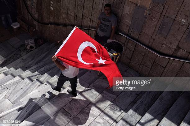 A supporter of Turkish President Recep Tayyip Erdogan waves a flag during a rally in Fatih district on July 19 2016 in Istanbul Turkey Clean up...