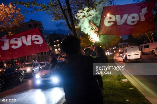 A supporter of Turkish President waves flags reading 'yes' near the headquarters of the conservative Justice and Development Party on April 16 2017...