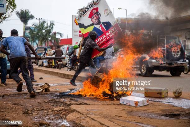 Supporter of Ugandan musician turned politician Robert Kyagulanyi, also known as Bobi Wine, carries his poster as they protest on a street against...