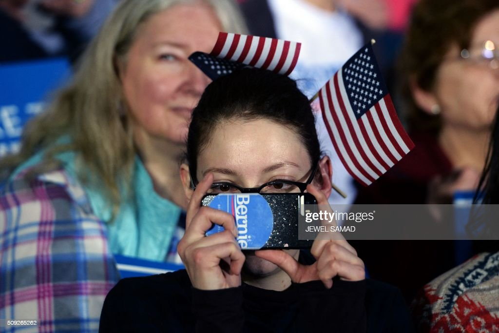 A supporter of US Democratic presidential candidate Bernie Sanders takes pictures as she arrives for primary night rally in Concord, New Hampshire, on February 9, 2016. / AFP / JEWEL