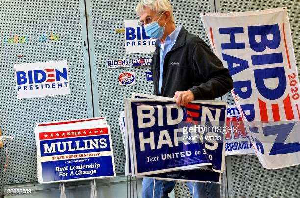 Supporter of US Democratic presidential candidate Joe Biden and his vice presidential running mate, US Senator Kamala Harris carries political signs...