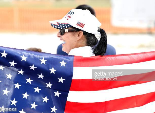 A supporter of US President Donald Trump brandishes a US flag at a rally at the Orlando Melbourne International Airport on February 18 2017 / AFP /...