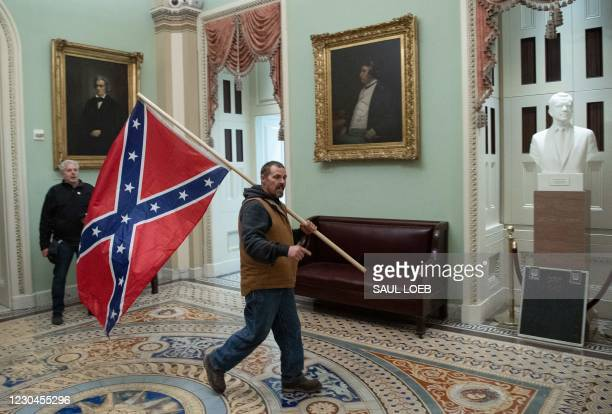 Supporter of US President Donald Trump carries a Confederate flag as he protestS in the US Capitol Rotunda on January 6 in Washington, DC. -...