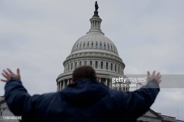 Supporter of US President Donald Trump challenging the results of the 2020 US Presidential election raises his arms outside the US Capitol on January...