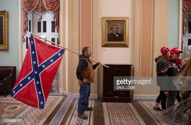 Supporter of US President Donald Trump holds a Confederate flag outside the Senate Chamber during a protest after breaching the US Capitol in...