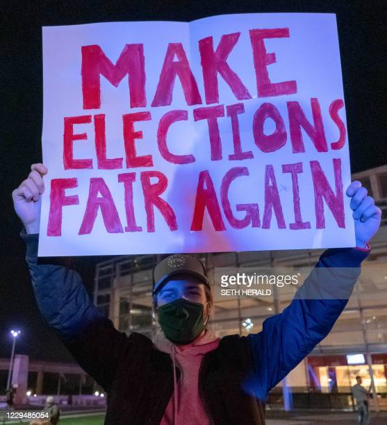 Supporter of US President Donald Trump holds a sign during a protest outside of the TCF Center where ballots are being counted, in Detroit, Michigan...