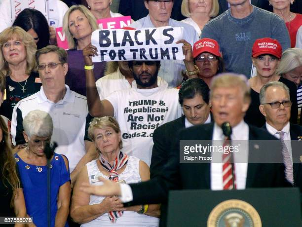 A supporter of US President Donald Trump holds up a sign as the president speaks to a crowd at the Phoenix Convention Center during a rally on August...