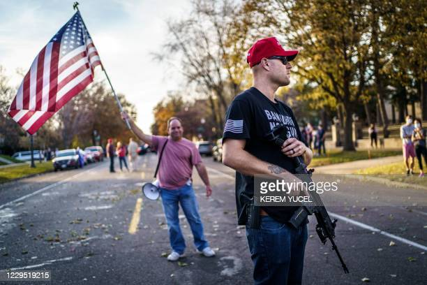 "Supporter of US President Donald Trump keeps a hand on his gun during a ""Stop the Steal rally"" in front of the residence of Minnesota Governor Tim..."