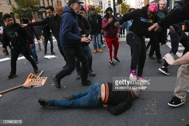 TOPSHOT A supporter of US President Donald Trump lying on the floor is kicked as he is attacked by antiTrump demonstrators in Black Lives Matter...