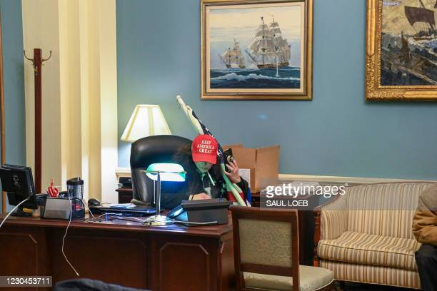 Supporter of US President Donald Trump sits inside the office of Speaker of the House Nancy Pelosi as he protest inside the US Capitol in Washington,...