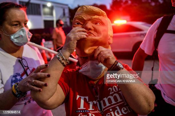 Supporter of US President Donald Trump wears a mask prior to his arrival for an NBC News town hall event at the Perez Art Museum in Miami on October...