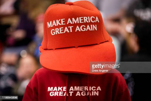 A supporter of US President Donald Trump wears an oversize Make America Great Again Hat as he waits for the start of a Keep America Great rally at...