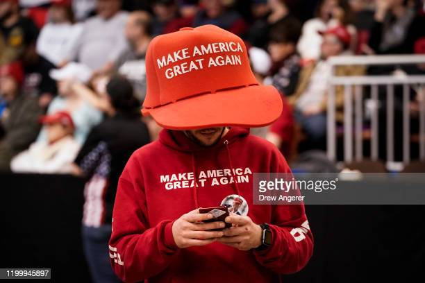 """Supporter of U.S. President Donald Trump wears an oversize """"Make America Great Again Hat"""" as he waits for the start of a """"Keep America Great"""" rally..."""