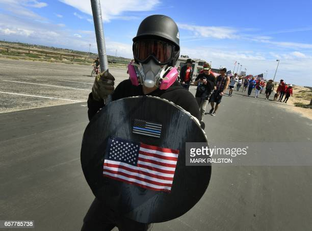 A supporter of US President Trump marches during the Make America Great Again rally in Huntington Beach California on March 25 2017 / AFP PHOTO /...