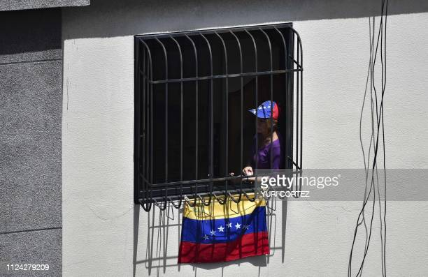 A supporter of Venezuelan opposition leader and self declared acting president Juan Guaido listens to his speech from the window of a building during...
