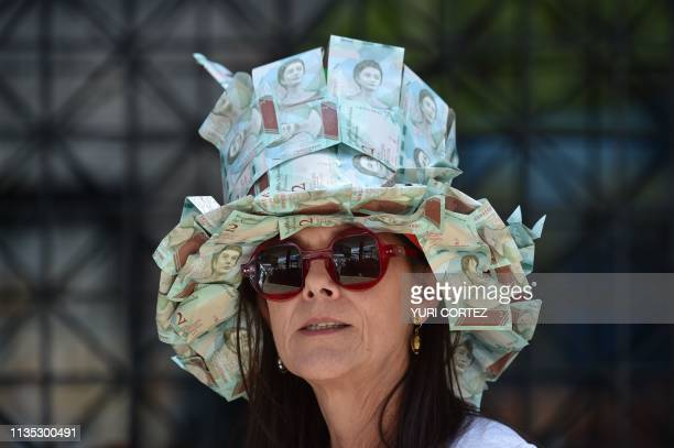Supporter of Venezuelan opposition leader and self-proclaimed interim president Juan Guaido wears a hat make of Bolivar banknotes during a demo in...