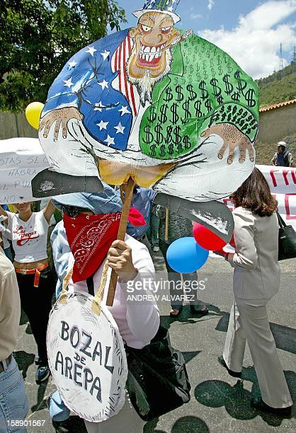 A supporter of Venezuelan President Hugo Chavez carrying a sign portraying Uncle Sam protests outside local television station Globovision in Caracas...