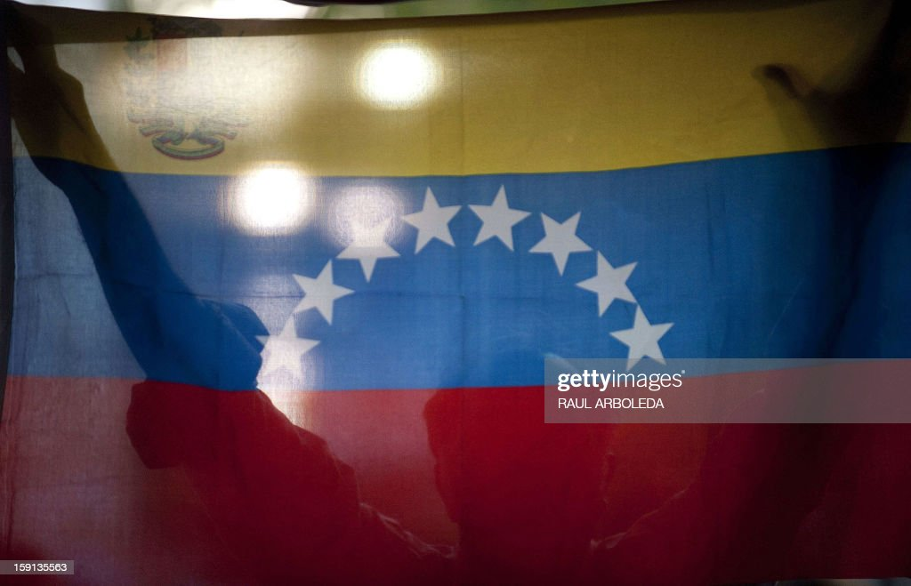A supporter of Venezuelan President Hugo Chavez holds a Venezuelan flag during a session of the National Assembly in Caracas on January 8, 2013. The President of the National Assembly Diosdado Cabello announced today that due to health reasons, Chavez will not be able to take the oath to be sworn in for a fourth term in office next January 10. A constitutional fight intensified with the government planning a massive show of support in the streets on the day he is supposed to be sworn in. Chavez, who underwent his fourth round of cancer surgery in Havana nearly a month ago, is suffering from a severe pulmonary infection that has resulted in a respiratory insufficiency. AFP PHOTO/Raul ARBOLEDA