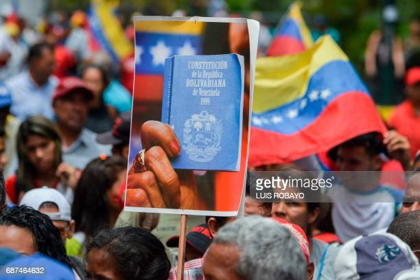 A supporter of Venezuelan President Nicolas Maduro holds a picture of the Constitution as he takes part in a rally in Caracas on May 23 in which...