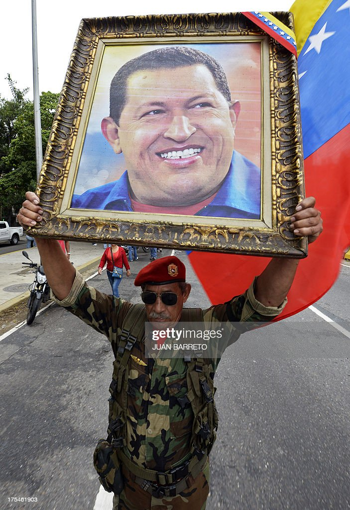 A supporter of Venezuelan President Nicolas Maduro holds a portrait of former Venezuelan President Hugo Chavez (1954-2013) during a demonstration in Caracas on August 3, 2013. Maduro and opposition leader Henrique Capriles leaded Saturday simultaneous demos against corruption. AFP PHOTO