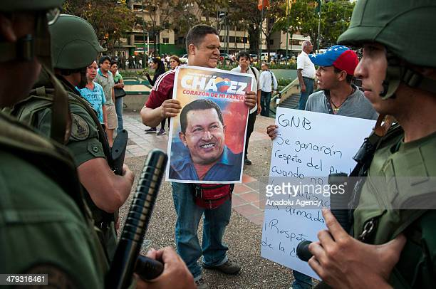 A supporter of Venezuelan President Nicolas Maduro holds a sign next to an opposition protestor at the Altamira square in Caracas Venezuuela on March...