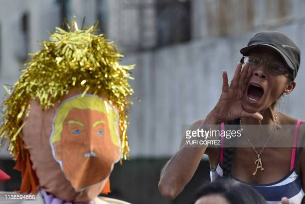 A supporter of Venezuelan President Nicolas Maduro shouts slogans as a dummy depicting US President Donald Trump is prepared to be burnt during the...