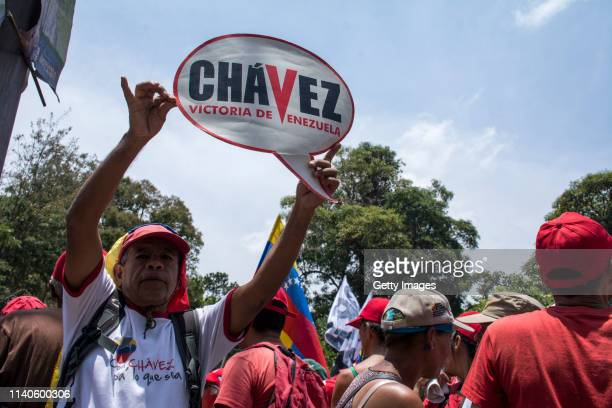Supporter of Venezuelan President Nicolás Maduro holds a banner that reads 'Chavez victory of Venezuela' during a demonstration on May 1 2019 in...