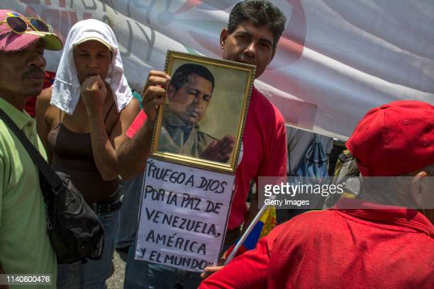 Supporter of Venezuelan President Nicolás Maduro holds a banner with a picture of late Venezuelan President Hugo Chavez that reads 'I pray to God for...