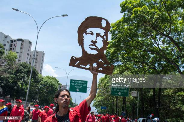 Supporter of Venezuelan President Nicolás Maduro holds a cardboard cutout of late Venezuelan President Hugo Chavez during a demonstration on May 1...