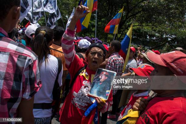 Supporter of Venezuelan President Nicolás Maduro holds a picture of late Venezuelan President Hugo Chavez during a demonstration on May 1 2019 in...