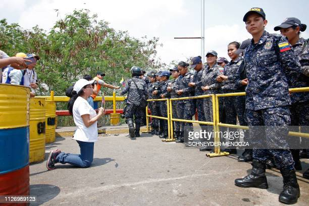 A supporter of Venezuela's opposition leader Juan Guaido kneels in front of members of Venezuela's Bolivarian National Police standing guard at the...