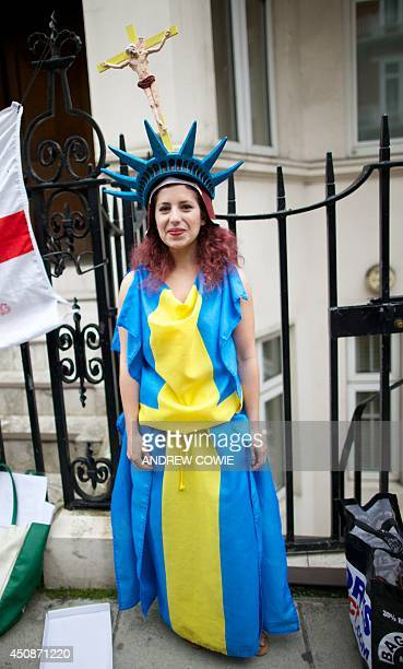 A supporter of WikiLeaks founder Julian Assange wearing a Swedish flag a hat resembling the Statue of Liberty and a Cross with Julian Assange in...