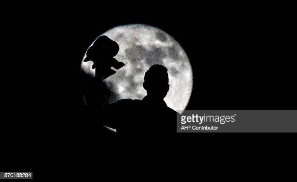 A supporter of Wydad Casablanca is silhouetted by the moon during the CAF Champions League final football match between Egypt's AlAhly and Morocco's...