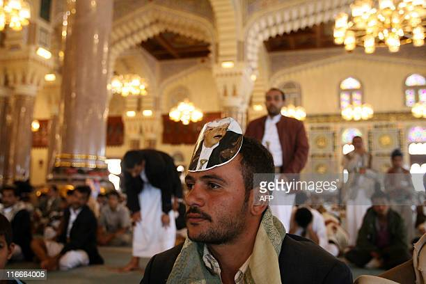 A supporter of Yemeni President Ali Abdullah Saleh wears a portrait of him on his forehead during Friday prayers at alSaleh mosque in Sanaa on June...