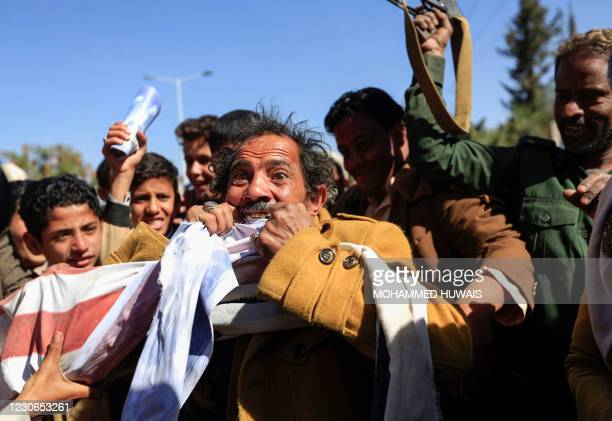 Supporter of Yemen's Huthi movement tears an Israeli flag with his teeth during a demonstration near the closed US embassy in the capital Sanaa, on...