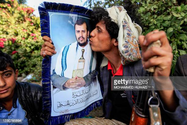 Supporter of Yemen's Huthi rebels kisses a portrait of their leader Abdulmalik Badreddin al-Huthi during a rally denouncing the United States and the...