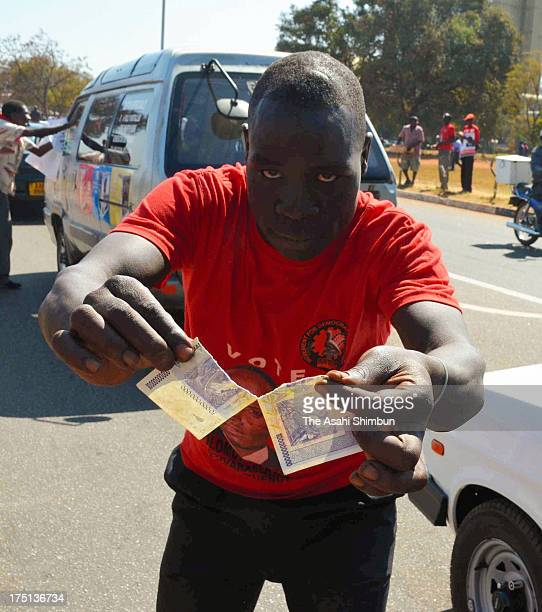A supporter of Zimbabwean Prime Minister Morgan Tsvangirai tears off the 10 billion Zimbabwean Dollars note in protest against President Robert...