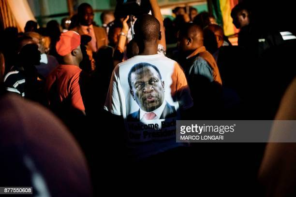 TOPSHOT A supporter of Zimbabwe's incoming president Emmerson Mnangagwa wears a tshirt with his portrait at Zimbabwe's ruling ZanuPF party...