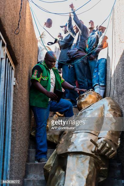 A supporter of Zimbabwe's ruling ZANU PF party stands next to a fallen statue of President Robert Mugabe on August 30 2017 in Harare in a show of...