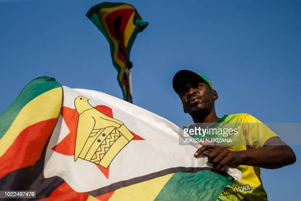 A supporter of Zimbabwe's ruling ZANUPF party wave the national flag after Zimbabwe's top court threw out an opposition bid to overturn presidential...
