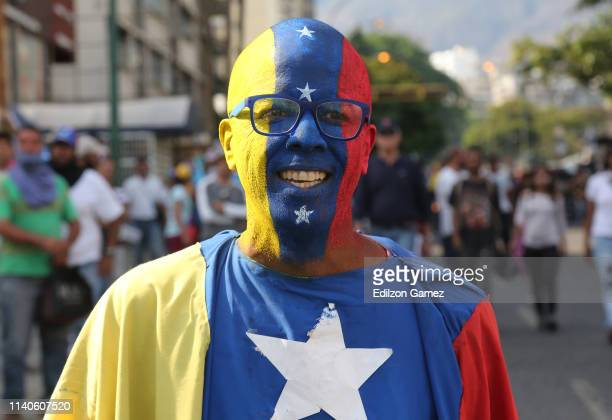 A supporter or Juan Guaido with his face painted and dressed with the colors of the Venezuelan flag smiles during the May 1 demonstration at avenida...