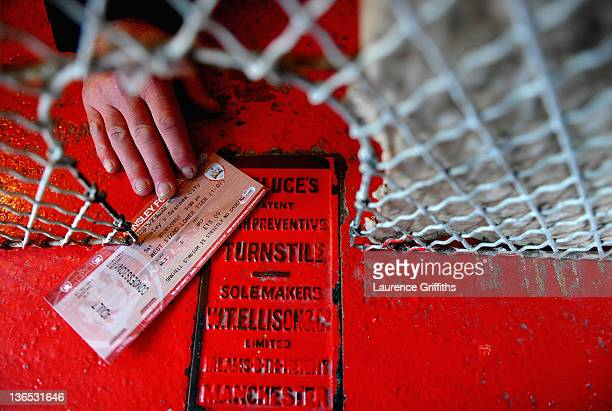 A supporter passes his match ticket over at a turnstile in the stadium prior to kick off during the FA Cup Third Round match sponsored by Budweiser...
