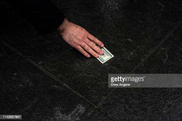 A supporter picks up a fake 1000 dollars bill representing Democratic presidential candidate Andrew Yang's plan for a $1000 monthly universal basic...