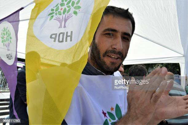 A supporter poses for a photo behind a party flag during the opening of a new election campaign booth of the proKurdish Peoples' Democractic Party...