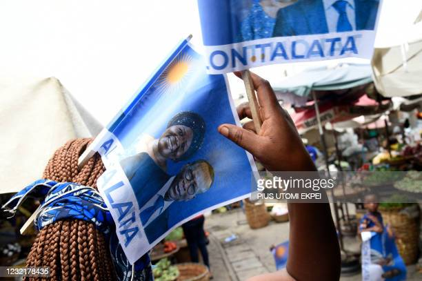 Supporter puts flags into her hair with photographs of incumbent Benin President Patrice Talon and running mate Mariam Talata at the market in...