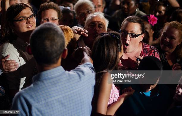 A supporter reacts after shaking hands with US President Barack Obama as he works the rope line after delivering remarks during a campaign event at...