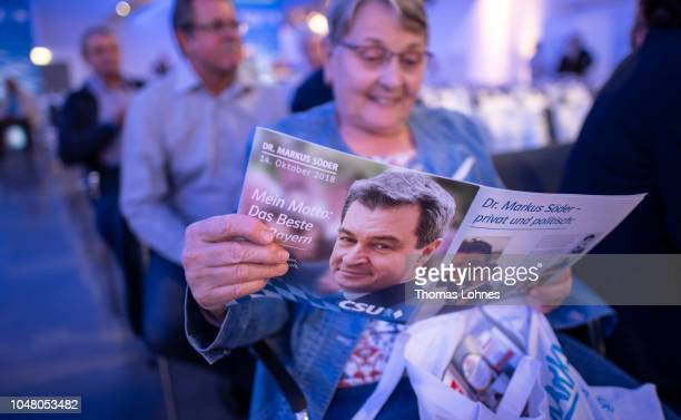 A supporter reads a flyer of Markus Soeder Governor of Bavaria and lead candidate for the Bavarian Social Union the Bavarian Christian Democrats at a...