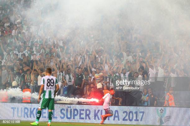Supporter runs with a burning flare as football fans invade the pitch during the Turkish Super Cup final football match between Besiktas and...