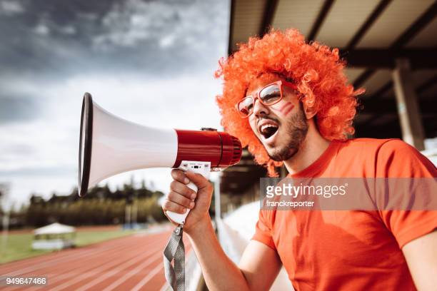 supporter screaming with megaphone at the stadium - wig stock pictures, royalty-free photos & images