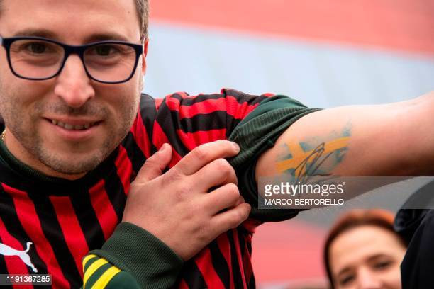 Supporter shows a tattoo with the Swedish national colours and a signature of Zlatan Ibrahimovic during the official presentation of Ibrahimovic as...